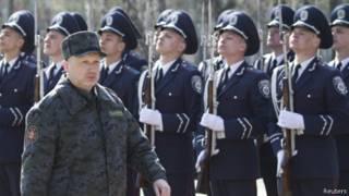 Исполняющий обязанности президента Украины Александр Турчинов  маришиорует на фоне украинских военных