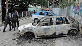 Policiais passam perto de carro incendiado na favela do Cantagalo (foto: AFP)