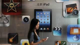 Cliente passe em frente a uma loja da Apple na China (Foto: AFP)