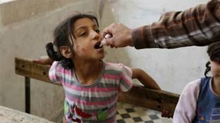 Ativista aplica vacina contra pólio em criança de Aleppo, na Síria (Reuters)