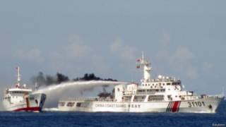 वियतनामी कोस्ट गार्ड के एक जहाज पर पानी की बौछार करता एक चीनी जहाज