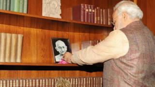अपने कार्यालय में महात्मा गांधी को फूल चढ़ाते प्रधानमंत्री नरेंद्र मोदी