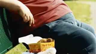 Persona obesa comiendo comida rápida.