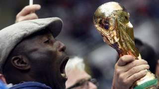 Hombre grita frente a modelo de la copa del Mundo