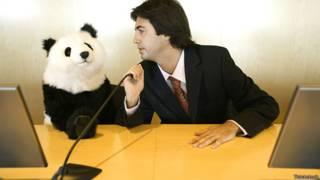 Бизнесмен дает советы чучелу панды