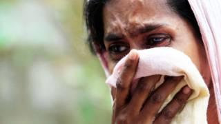 Una mujer llora frente a su casa quemada por budistas radicales