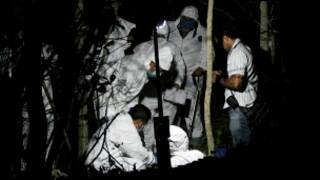 Peritos forenses trabajan en una fosa clandestina. Foto Getty Images.