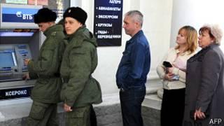 Soldados y civiles hacen cola para retirar dinero en un banco ruso en Crimea