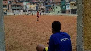 Meninos jogam futebol em campo de terra no Capão Redondo, em SP