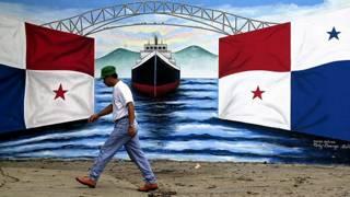 Hombre camina ante mural con bandera panameña