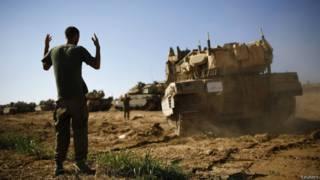 Soldado israelí dirige el movimiento de un tanque en Gaza