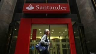Una mujer pasa por la puerta de una sucursal del banco Santander en Brasil