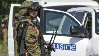 Пророссийский сепаратист наблюдает за автомобилем миссии ОБСЕ