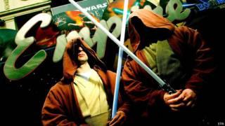 Dos hombres vestidos con la capa característica de los Jedis y portando espadas de luz