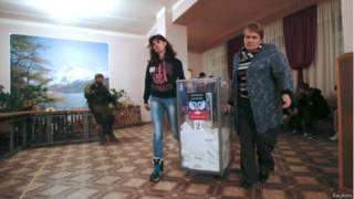 Члены местной избирательной комиссии в Донецке несут урну с бюллетенями после голосования 2 ноября 2014 г.