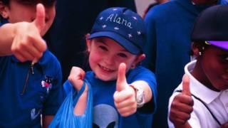 school children thumbs up