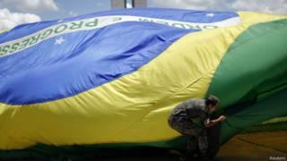 Soldado hasteia bandeira em Brasília (Foto: Reuters)
