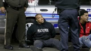 अमरीका में विरोध प्रदर्शन कर रहे काले युवकों को पकड़ती पुलिस