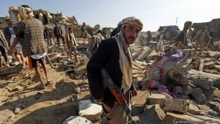 Повстанец-хусит в Йемене у развалин домов, уничтоженных в ходе авиаударов сил коалиции во главе с Саудовской Аравией