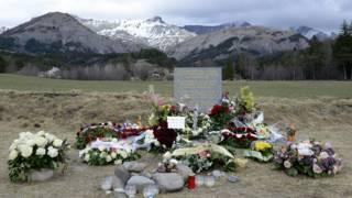 Цветы у мемориального камня в память погибших пассажиров Germanwings