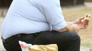 رجل سمين يتناول وجبة سريعة