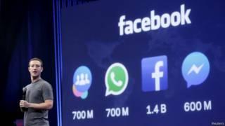 मार्क ज़करबर्ग फ़ेसबुक के लोगो के सामने