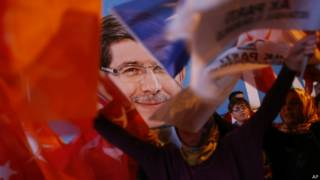 तुर्की के प्रधानमंत्री के पोस्टर के सामने झंडे लहराते समर्थक
