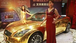 Un auto dorado en exhibición, con unas modelos chinas