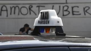 """Такси на фоне стены с надписью """"Смерть Uber"""""""