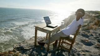 Экспат на морском берегу, с ноутбуком