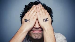 Человек закрыл лицо ладонями с нарисованными на них глазами