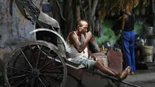 Индийский рикша пьет чай на городской улице