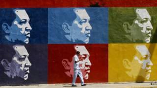 Una persona pasa frente a un mural con rostros de Chávez