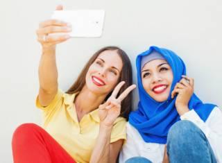 Европейская и мусульманская девушка делают сэлфи