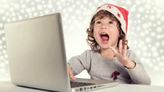 Un niño con gorro de navidad feliz frente a una laptop