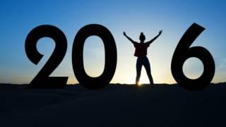 """Una persona alza los brazos en medio del número """"2016"""""""