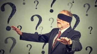Un hombre con los ojos vendados camina entre signos de interrogación