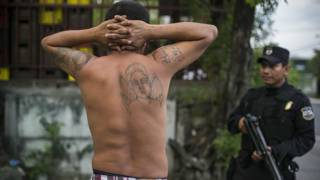 Un policía detiene a un hombre en El Salvador