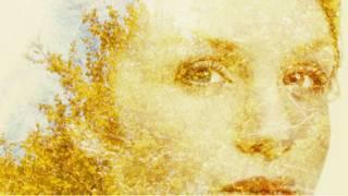 El rostro de una mujer confundido con las hojas de un árbol en otoño