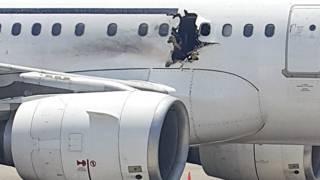 मोगादिशू के अदन अब्दुल अंतरराष्ट्रीय हवाई अड्डे पर खड़ा विमान.
