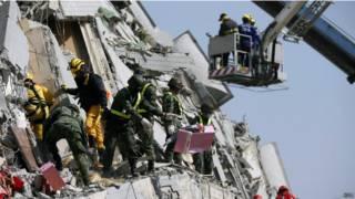 इमारत के पास राहत और बचाव काम करते कर्मचारी.