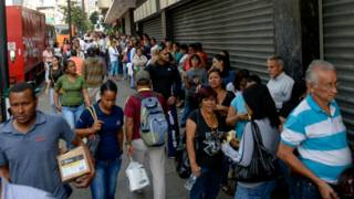 Ciudadanos en cola en una calle de Caracas.