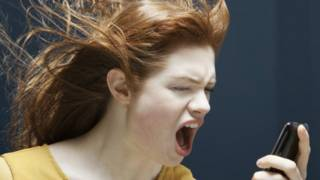 Una mujer le grita a un teléfono celular