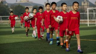 Niños chinos jugando al fútbol