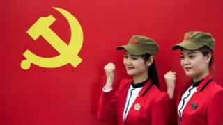 Du khách chụp ảnh trước cờ Đảng Cộng sản Trung Quốc