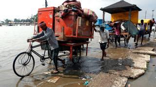 इलाहाबाद में गंगा का पानी बढ़ने के बाद अपना सामान हटाते लोग.