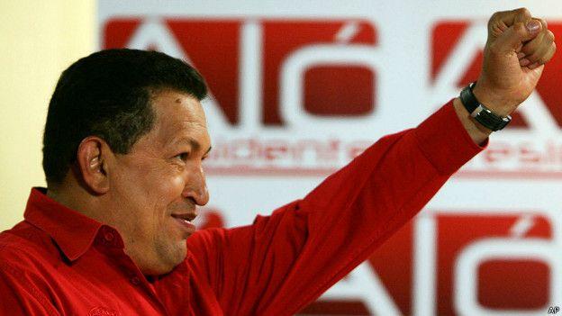 El fallecido presidente venezolano Hugo Chávez alza su puño izquierdo.
