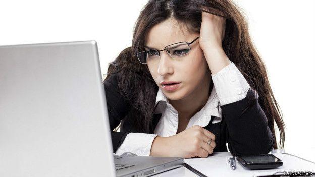 Una mujer mirando una laptop con cara de desesperación