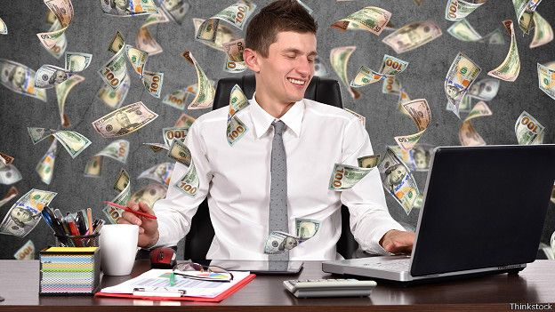Un hombre sonríe en una oficina mientras llueve dinero a su alrededor
