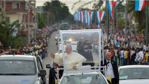 El papa saluda a personas congregadas en una gran avenida